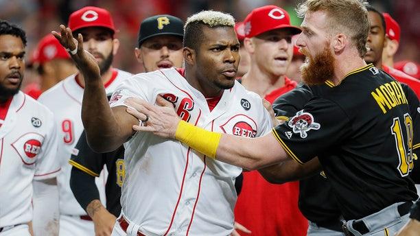 Cincinnati Reds' Yasiel Puig (66) is restrains by Pittsburgh Pirates third baseman Colin Moran (19) during the ninth inning of a baseball game Tuesday, July 30, 2019, in Cincinnati.