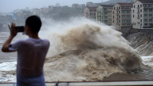 In this Aug. 9, 2019, photo released by Xinhua News Agency, a man uses his mobile phone to record waves crashing on the shore as typhoon Lekima approaches the Shitang Township of Wenling City in eastern China's Zhejiang Province. Typhoon Lekima stuck the coast south of Shanghai, knocking down houses and trees.