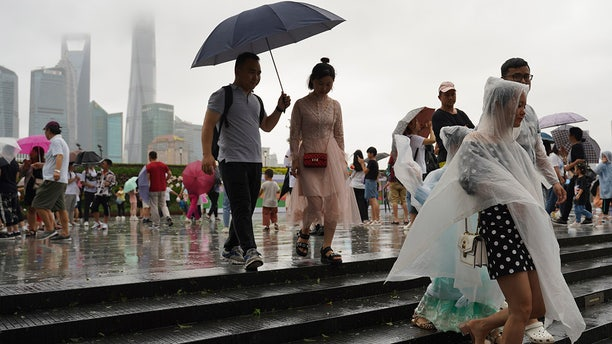 Visitors leave from the bund as Typhoon Lekima approaches in Shanghai Saturday, Aug. 10, 2019. Typhoon Lekima has struck China's coast south of Shanghai, knocking down trees and forcing airlines to cancel flights.