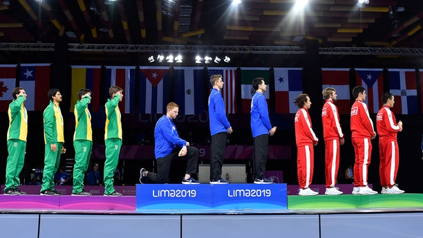 In this Friday, Aug. 9, 2019 photo, released by Lima 2019 News Services, Race Imboden of the United States takes a knee, as teammates Mick Itkin and Gerek Meinhardt stand on the podium after winning the gold medal in team's foil, at the Pan American Games in Lima, Peru. (Jose Sotomayor/Lima 2019 News Services via AP)
