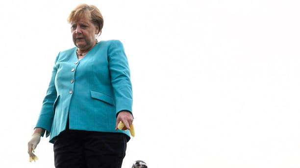 German Chancellor Angela Merkel stands next to a penguin after feeding it a treat, on the roof of the Ozeaneum in Stralsund, Germany, Tuesday, Aug. 13, 2019.
