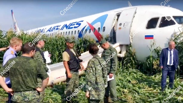 In this file image taken from a video distributed by Russian Investigative Committee, Investigative Committee employees work at the crash site of a Russian Ural Airlines' A321 plane is seen after an emergency landing in a cornfield near Ramenskoye, outside Moscow, Russia, Thursday, Aug. 15, 2019.