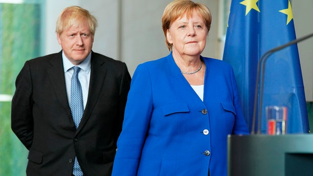 """Germany's Chancellor Angela Merkel and British Prime Minister Boris Johnson arrive for a joint press conference, in Berlin, Wednesday, Aug. 21, 2019. German Chancellor Angela Merkel says she plans to discuss with UK Prime Minister Boris Johnson how Britain's exit from the European Union can be """"as frictionless as possible."""""""