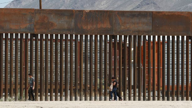 In this July 17, 2019 photo, three migrants who had managed to evade the Mexican National Guard and cross the Rio Grande onto U.S. territory walk along a border wall set back from the geographical border, in El Paso, Texas. (AP Photo/Christian Chavez, File)