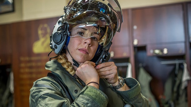 Capt. Anneliese Satz puts on her flight helmet prior to a training flight aboard Marine Corps Air Station Beaufort.  (U.S. Marine Corps photo by Sgt. Ashley Phillips)