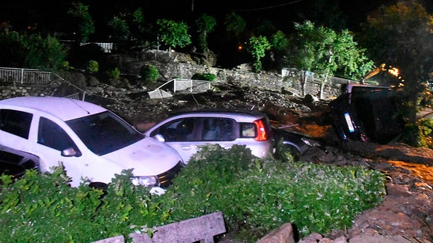 Capsized cars as seen the roads of after they were hit by a landslide in Casargo, near the Italian town of Lecco, in the early hours of Wednesday, Aug. 7.