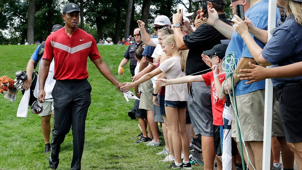 Tiger Woods, left, greets fans as he walks to the 14th fairway after hitting his tee shot during the final round of the BMW Championship golf tournament at Medinah Country Club, Sunday, Aug. 18, 2019, in Medinah, Ill. (AP Photo/Nam Y. Huh)