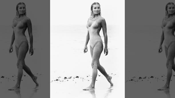 """Actress Bo Derek, with her hair in cornrows, walks along the beach in swimwear as Samantha Taylor in the 1979 movie """"10,"""" directed by Blake Edwards."""