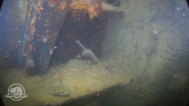 Bottles and other artifacts on a shelf in a cabin on HMS Terror's lower deck. (Parks Canada, Underwater Archaeology Team)