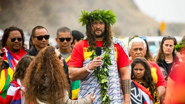 Actor Jason Momoa addresses elders as he visits Native Hawaiian protesters blocking the construction of a giant telescope on Hawaii's tallest mountain, at Mauna Kea Access Road on Wednesday, July 31, 2019, in Mauna Kea, Hawaii. (Associated Press)