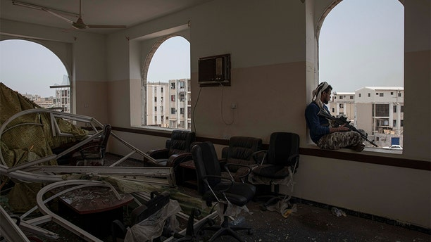 A soldier guards the site of a deadly attack inside the Sheikh Othman police station in Aden, Yemen, Thursday, Aug. 1, 2019. Yemen's rebels have fired a ballistic missile at a military parade in the southern port city of Aden as coordinated suicide bombings targeted the police station in another part of the city. The attacks killed at least 51 people and wounded dozens.