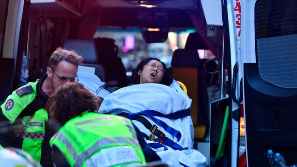 A women is taken by ambulance from Hotel CBD at the corner of King and York Street in Sydney, after a young man yelling about religion and armed with a knife attempted to stab several people.