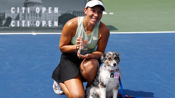 Jessica Pegula poses with a trophy and her dog Maddie after defeating Camila Giorgi, of Italy, in a final match at the Citi Open tennis tournament, Sunday, Aug. 4, 2019, in Washington. (AP Photo/Patrick Semansky)