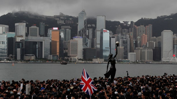 In this Sunday, July 7, 2019, photo, thousands of protesters carrying the British flag march near the harbor of Hong Kong. Hong Kong police on Tuesday confirmed it had received a report on Aug. 9, 2019, about a British foreign ministry employee who has been missing since crossing into China on a business trip.