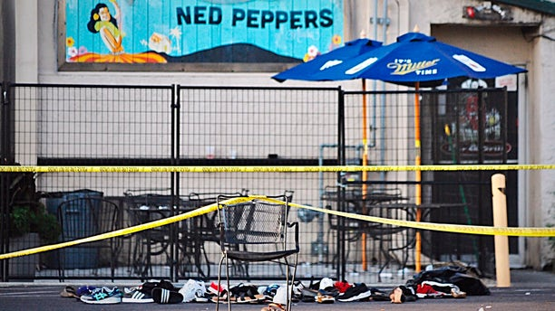 Police tape drapes over a chair near a pile of shoes after a mass shooting in Dayton, Ohio on Sunday, Aug, 4, 2019.