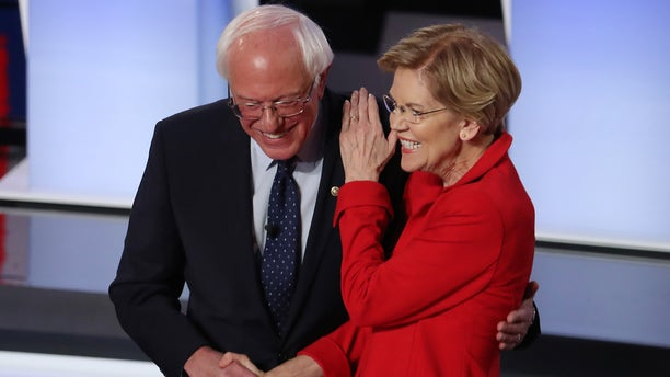 Democratic presidential candidate Sen. Bernie Sanders (I-VT) and Sen. Elizabeth Warren (D-MA) greet each other at the start of the Democratic Presidential Debate at the Fox Theatre in Detroit on July 30, 2019.