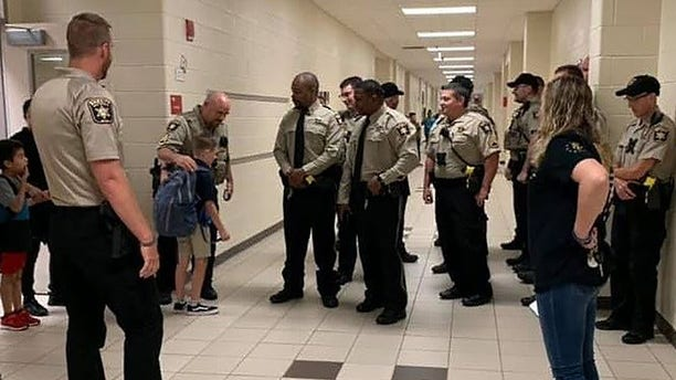 Caden Dixon, 9, is escorted to his class by the Hall County Sheriff's Office.