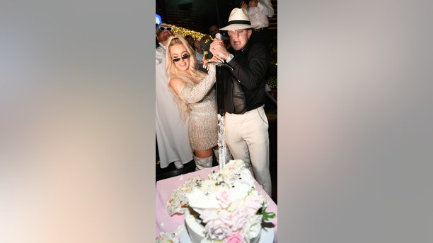 Jake Paul and Tana Mongeau cut their cake with a sword at their wedding reception at Sweet Beginnings in Sugar Factory on July 28, 2019 in Las Vegas, Nevada.