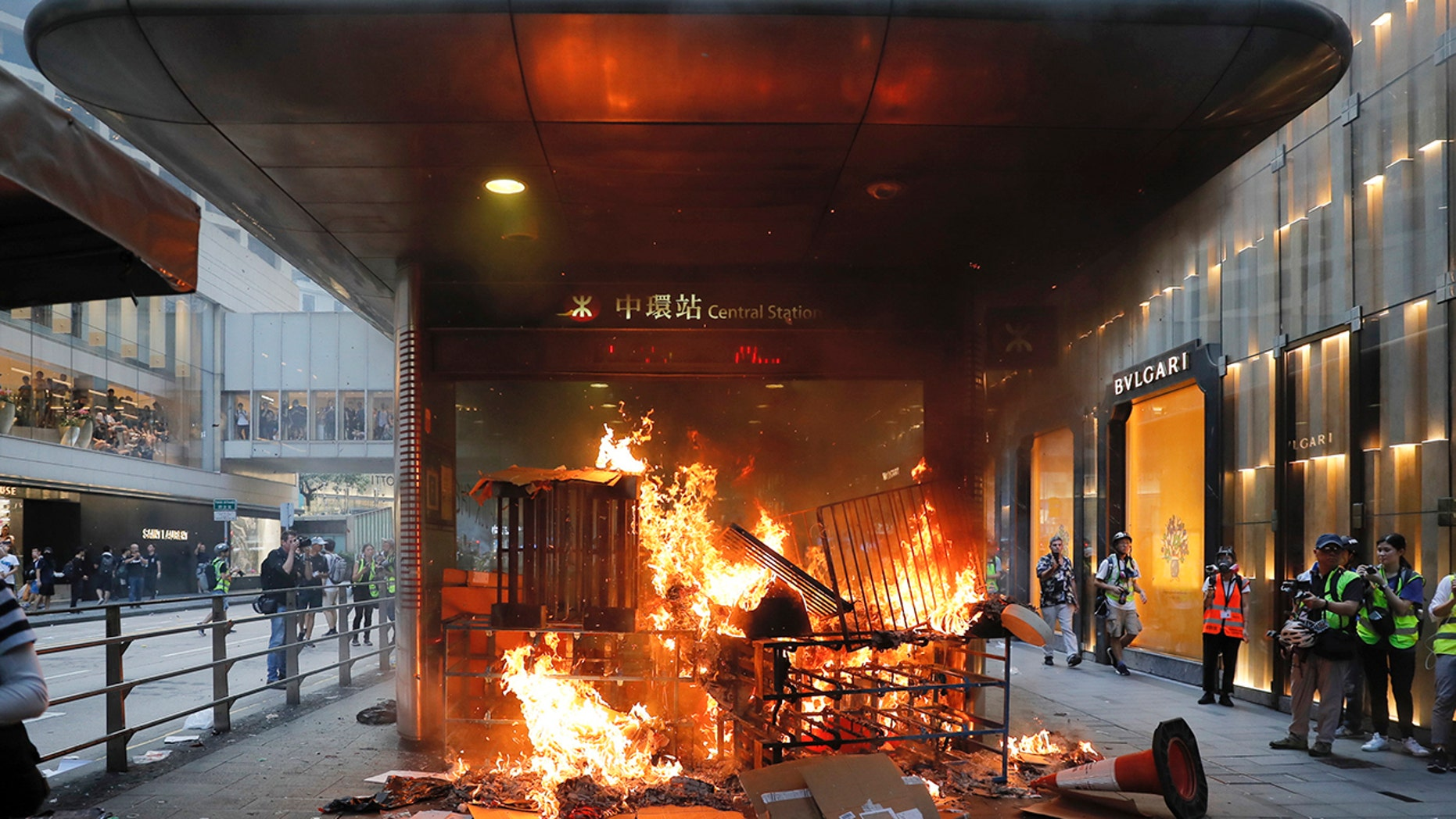 In this Sunday, Sept. 8, 2019, file photo, a fire set by protesters burns at an entrance to the Central MTR subway station in Hong Kong. Thousands of demonstrators participated in a peaceful march to the U.S. Consulate but later violence broke out in the business and retail but later after protesters vandalized a metro station and blocked traffic at a major thoroughfare, with several people detained. (AP Photo/Kin Cheung, File)