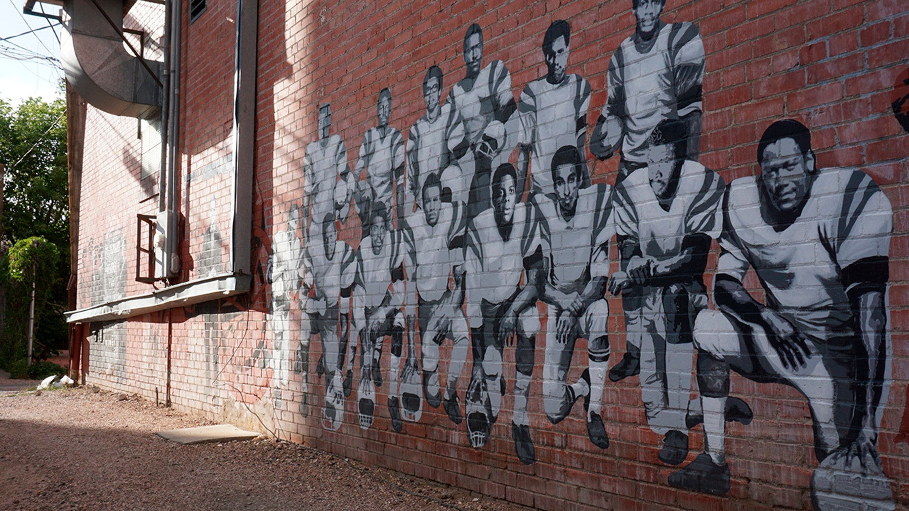 In this Wednesday, Sept. 11, 2019 photo shows part of an alleyway mural in downtown Laramie, Wyo., that honors the Black 14. The Black 14 were black athletes dismissed from the University of Wyoming football team in 1969 for seeking to protest racism by wearing black armbands in a game against Brigham Young University. The university plans to dedicate a plaque honoring the group at War Memorial Stadium on Friday. (AP Photo/Mead Gruver)