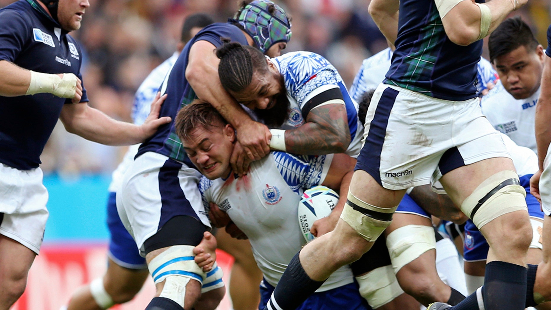 FILE - In this Oct. 10, 2015, file photo, Samoa's Jack Lam is tackled during their Rugby World Cup Pool B match between Samoa and Scotland at St James' Park, Newcastle, England. Samoan rugby players will wear skin suits to cover their traditional Pacific Islander tattoos during some training sessions at the World Cup in order not to offend their Japanese hosts. (AP Photo/Scott Heppell, File)