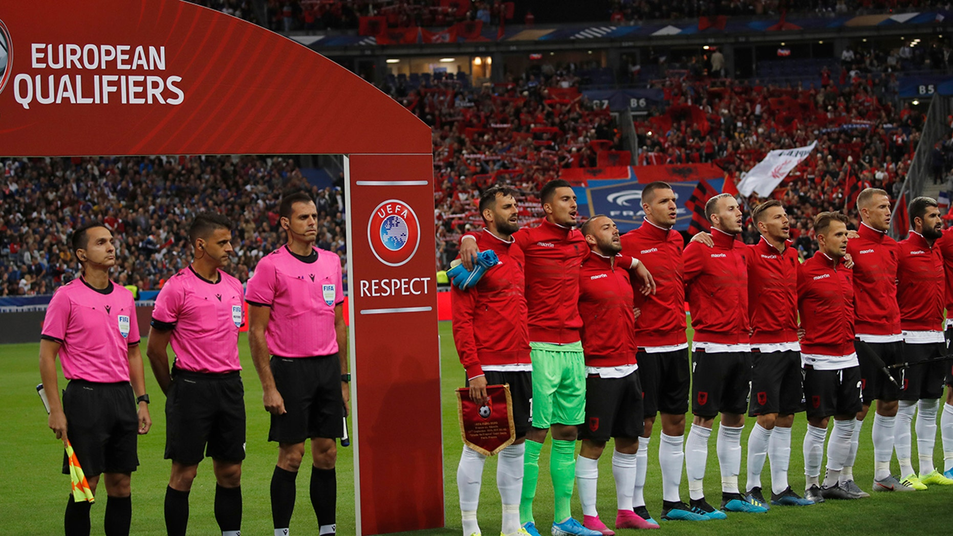 Referees and Albania's soccer team stand during Albania's national anthem, after the wrong one was playing, during of the Euro 2020 group H qualifying soccer match between France and Albania at the Stade de France in Saint Denis, north of Paris, France, Saturday, Sept. 7, 2019. (AP Photo/Christophe Ena)