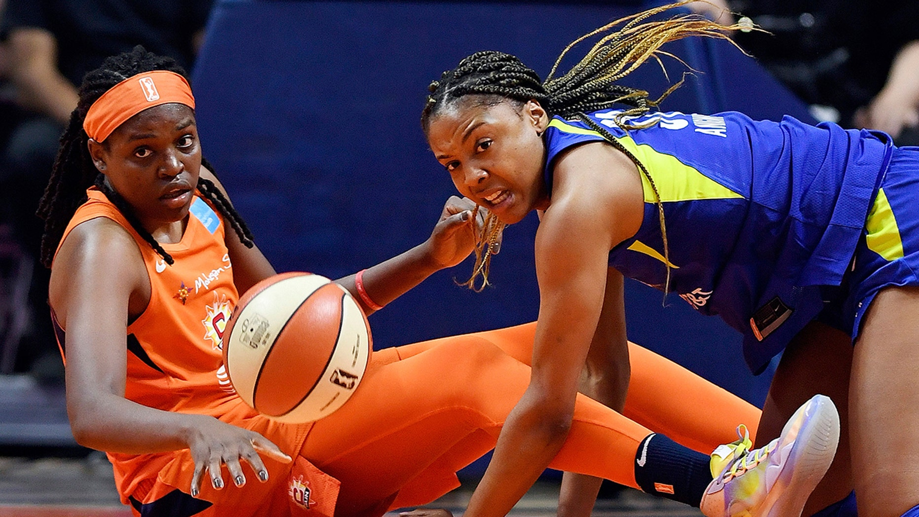 Connecticut Sun center Jonquel Jones, left, and Dallas Wings center Kristine Anigwe dive to the floor after a loose ball during a WNBA basketball game Wednesday, Sept. 4, 2019, in Uncasville, Conn. (Sean D. Elliot/The Day via AP)