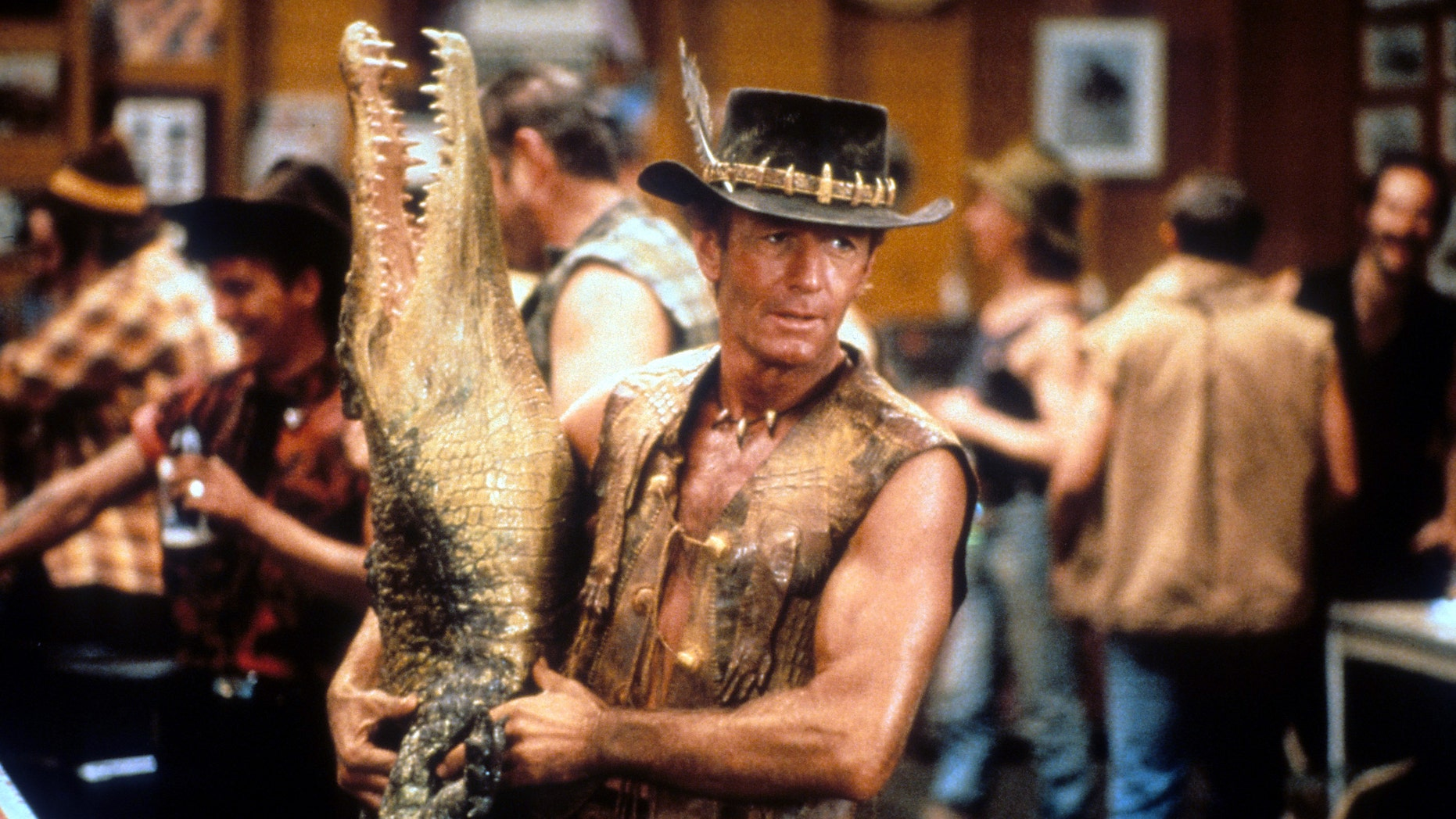 Paul Hogan carrying dead crocodile in bar in a scene from the film 'Crocodile Dundee', 1986. (Photo by Paramount/Getty Images)