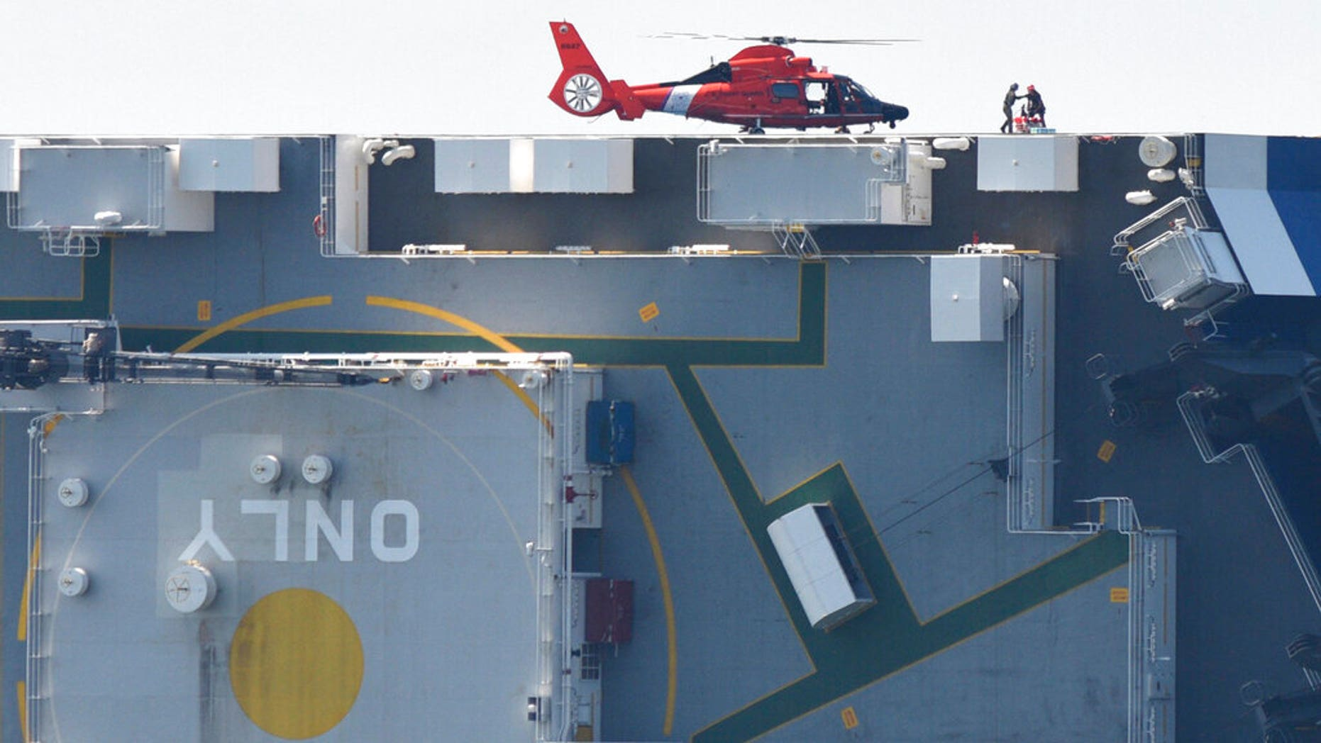 Members of the U.S. Coast Guard unload supplies from a Coast Guard helicopter from the side of the cargo ship Golden Ray, Monday(Bobby Haven/The Brunswick News via AP)