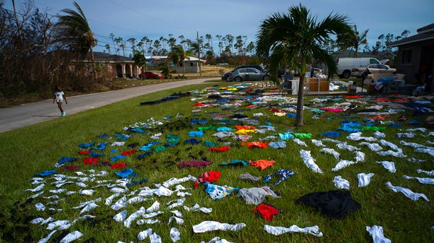 A child walks past clothes laid out to dry on a field in the aftermath of Hurricane Dorian, in the Arden Forest neighborhood of Freeport, Bahamas, Wednesday, Sept. 4, 2019. (Associated Press)