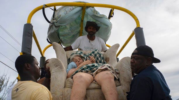 Sitting in her home's lounger, Virginia Mosvold, 84, is lowered from a truck by volunteers after being rescued from her flooded home on Ol' Freetown Farm farm in the aftermath of Hurricane Dorian before being taken to the hospital on the outskirts of Freeport, Bahamas, Wednesday, Sept. 4, 2019. (Associated Press)
