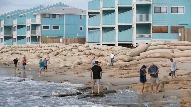 Beachgoers looks for shells in the aftermath of Hurricane Dorian in from of The Riggings beachfront condominiums at Kure Beach, N.C., Friday, Sept. 6, 2019.