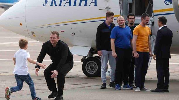 Ukraine's President Volodymyr Zelenskiy, right, greets Ukrainian prisoners upon their arrival at Boryspil airport, outside Kyiv, Ukraine, Saturday, Sept. 7, 2019.