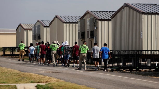 In this July 9, 2019, file photo, staff escort immigrants to class at the U.S. government's newest holding center for migrant children in Carrizo Springs, Texas. A federal judge on Friday blocked the Trump administration from ending the so-called Flores Settlement, a longstanding settlement governing detention conditions for immigrant children, including how long they can be held by the government. (AP Photo/Eric Gay, File)