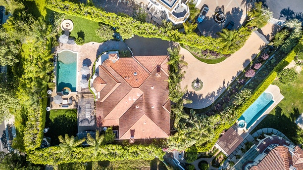 """Cuoco's old digs are situated on """"expansive resort-like grounds"""" that boast a """"sparkling pool, cascading water feature, fire pit, spa, [and] outdoor kitchen and bar"""" with plenty of room for entertaining on a large patio, plus a spacious """"car court"""" out front."""