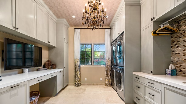 """Fancy features include a grand two-story foyer, sweeping staircase, a """"top shelf"""" suite of appliances in the kitchen, home theater, a """"tech-bar"""" room and fireplaces throughout."""