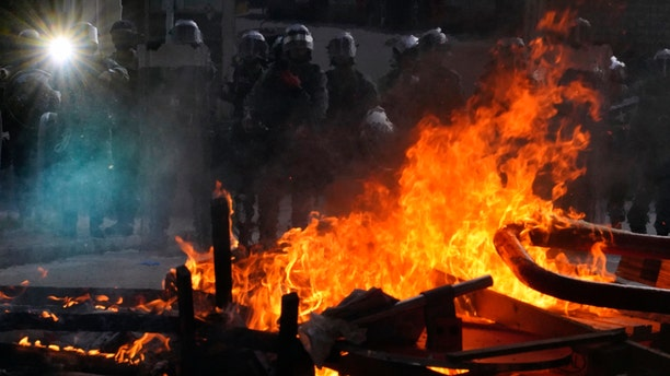 Police face a burning barricade during protests in Hong Kong on Saturday, Sept. 21, 2019. Protesters in Hong Kong burned a Chinese flag and police fired pepper spray Saturday in renewed clashes over grievances by the anti-government demonstrators. (AP Photo/Vincent Yu)