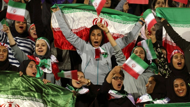 In this Oct. 16, 2018 file photo, Iranian women cheer as they wave their country's flag after authorities in a rare move allowed a select group of women into Azadi stadium to watch a friendly soccer match between Iran and Bolivia, in Tehran, Iran.