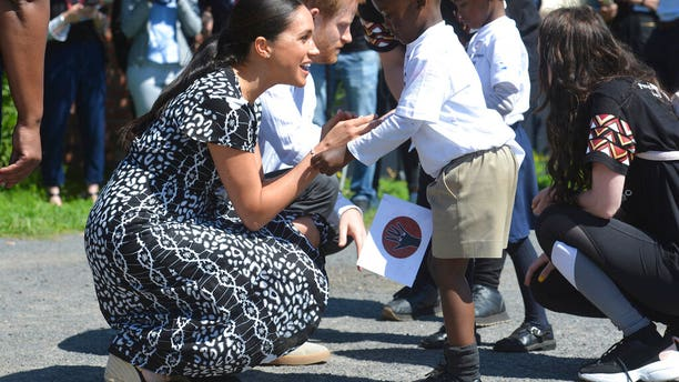 Prince Harry and Meghan Duchess of Sussex greet children on their arrival at the Nyanga Methodist Church in Cape Town, South Africa, in Sept. 2019.