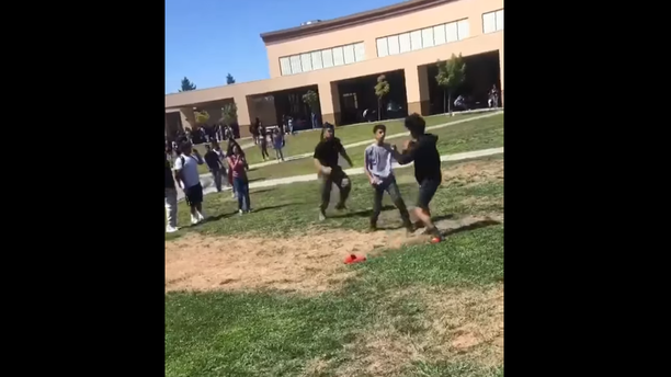 A U.S. Marine sprints to tackle two high school students in Stockton, Calif., to break up their fight. (Courtesy of 209 Times)