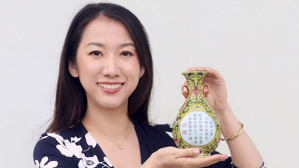 Sworders expert Yexue Li holding the vase, which was bought for £1 in a charity shop. (Credit: Sworders/BNPS)