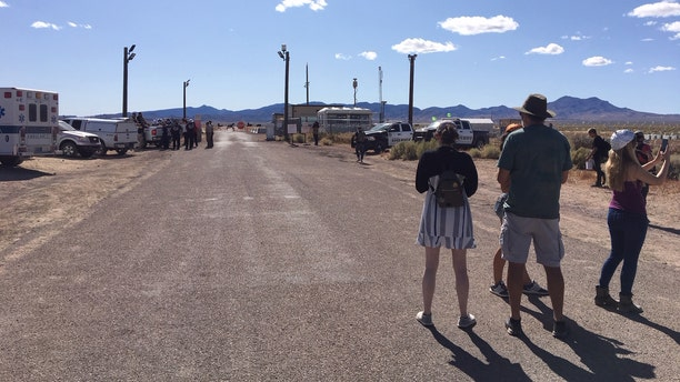 Onlookers take photos of the outside of the back gate to Area 51 as onlookers look on.