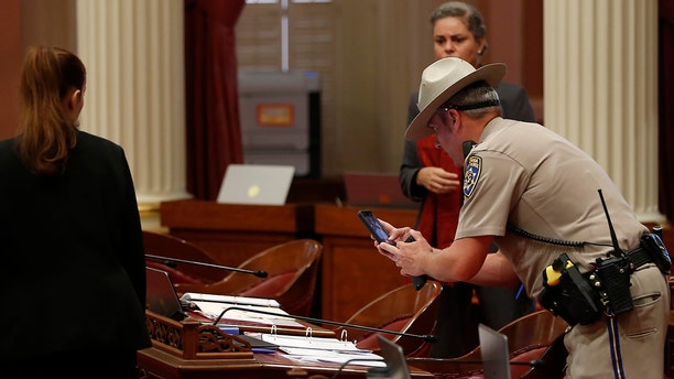 A California Highway Patrol Officer photographs a desk on the Senate floor after a red liquid was thrown from the Senate Gallery during the Senate session at the Capitol in Sacramento, Calif., Friday, Sept. 13, 2019. (Associated Press)