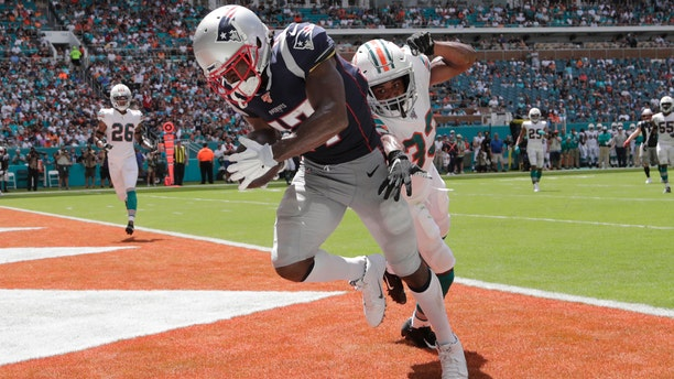 New England Patriots wide receiver Antonio Brown (17) scores a touchdown as Miami Dolphins cornerback Jomal Wiltz (33) attempts to defend, during the first half at an NFL football game, Sunday, Sept. 15, 2019, in Miami Gardens, Fla.