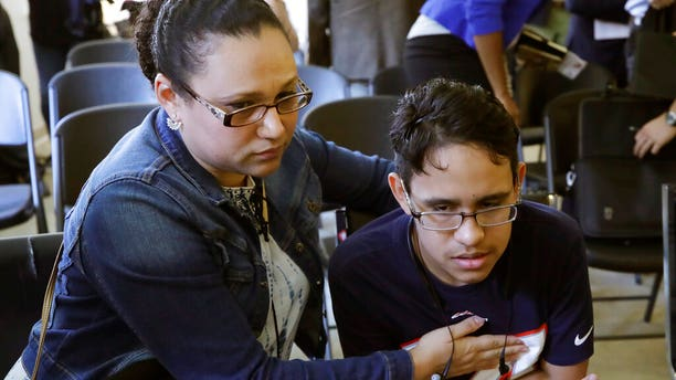 Mariela Sanchez, of Honduras, comforting her son, Jonathan, 16, during a news conference last week in Boston. The Sanchez family came to the United States seeking treatment for Jonathan's cystic fibrosis. (AP Photo/Elise Amendola)