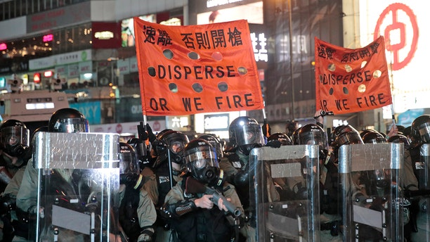 Police officers hold banners ordering protestors to disperse. Protesters made a wall out of barricades and set it afire. (AP Photo/Jae C. Hong)