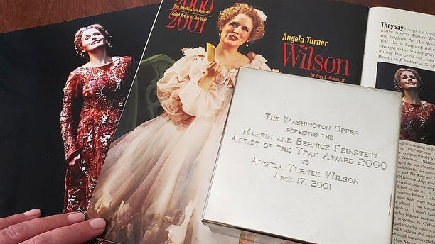 """Opera singer Angela TurnerWilson displays her 2000 Artist of the Year award from the Washington Opera next to a photo of herself from a 1999 performance of """"Le Cid,"""" left, and a magazine article in a Washington Opera magazine, at her home in Texas."""