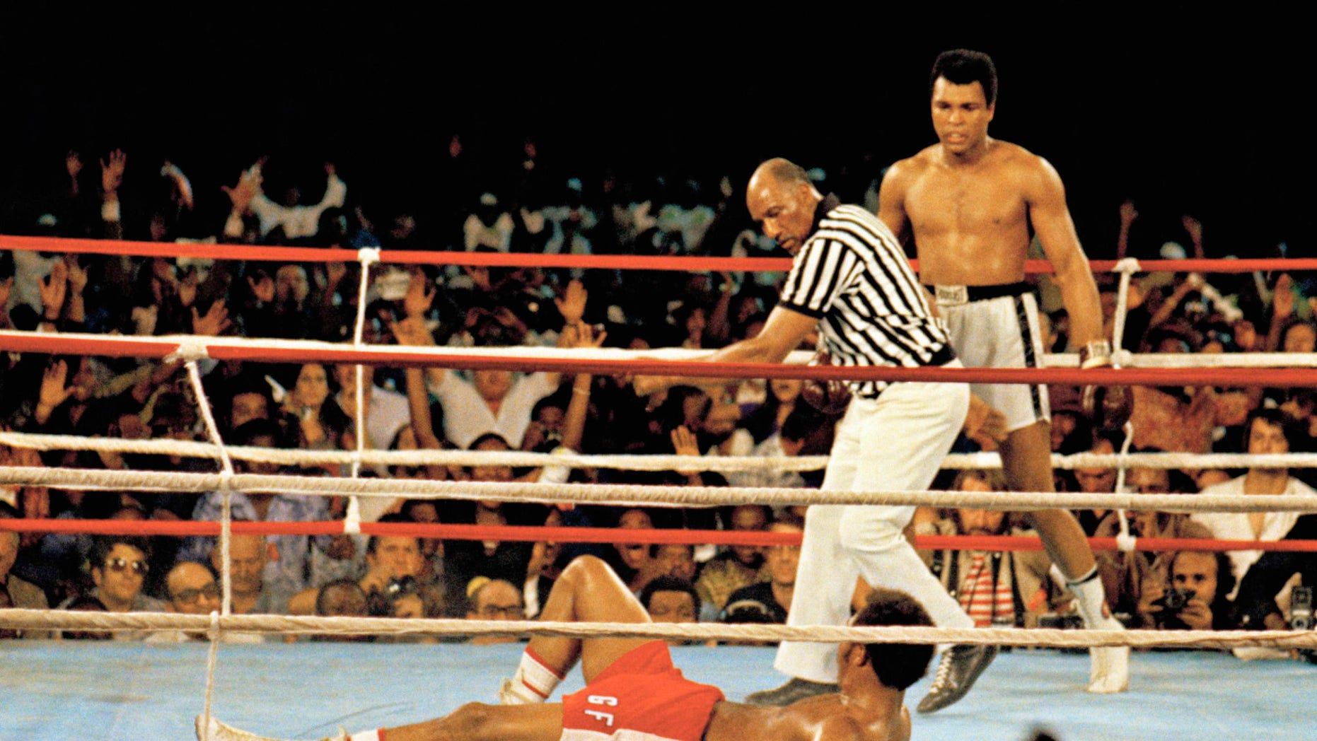 This is a Oct. 30, 1974 file photo of Muhammad Ali, reg, as he stands back as referee Zack Clayton calls the count over opponent George Foreman, red shorts, in Kinshasa, Zaire.  (AP-foto, lêer)