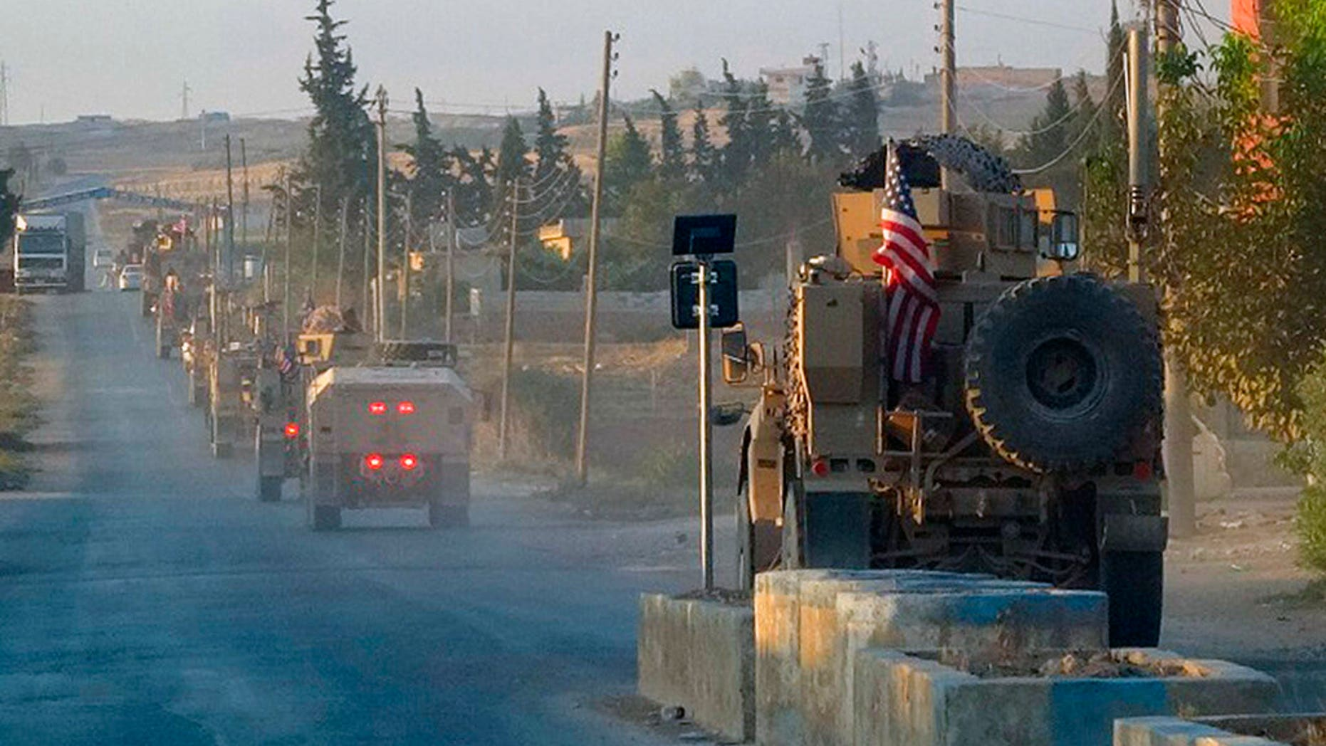 In this image provided by Hawar News Agency, ANHA, U.S. military vehicles travel down a main road in northeast Syria, Monday, Oct. 7, 2019. U.S.-backed Kurdish-led forces in Syria said American troops began withdrawing Monday from their positions along Turkey's border in northeastern Syria, ahead of an anticipated Turkish invasion. (ANHA via AP)