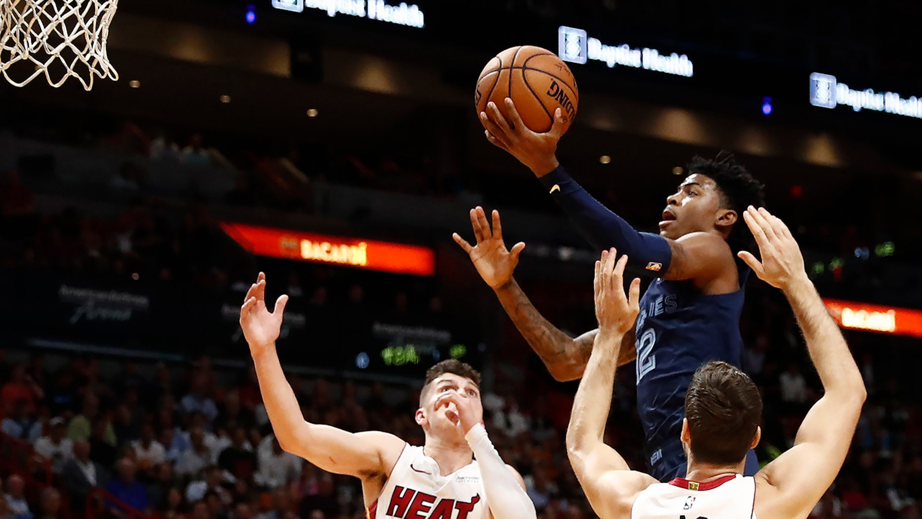 Memphis Grizzlies' Ja Morant (12) shoots as Miami Heat guards Tyler Herro (14) and Goran Dragic (7) defend during the first half of an NBA basketball game Wednesday, Oct. 23, 2019, in Miami. (AP Photo/Brynn Anderson)